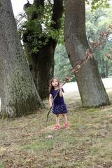 Kleines Mädchen hält einen großen Ast