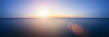 Conceptual image of sunset with added lens flare over still wate