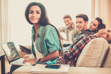 Students preparing for exams in apartment interior behind table