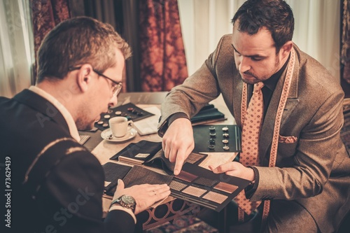 Tailor and client choosing mterials for custom made suit