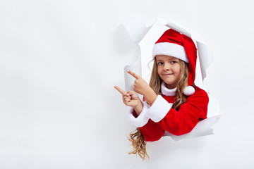 Girl in santa claus costume pointing to copy space