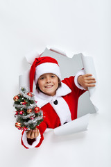 Happy christmas boy giving you a small decorated fir tree
