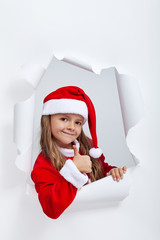 Little girl in Santa Claus outfit giving thums up sign