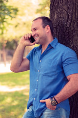 Man in a park smiling on the phone