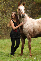 Beautiful girl with nice dress standing next to nice horse