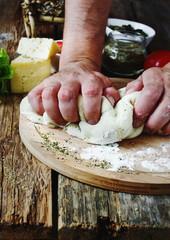 human hand knead pizza dough