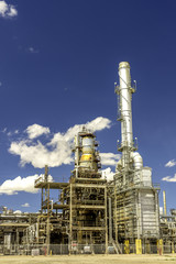 Oil power refinery with clouds and blue sky