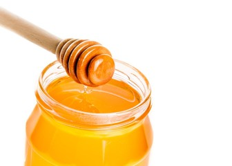 honey jar on white background with wooden honey dipper on top