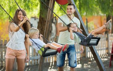 Smiling parents swinging children