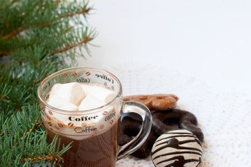 Cup of hot chocolate with marshmallows, cakes and fir branches.