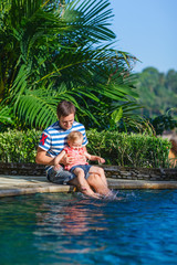Father and daughter near swimming pool