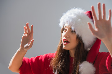 Christmas woman wearing Santa Claus hat working with virtual int
