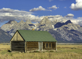 Tetons backdrop and rustic log cabin