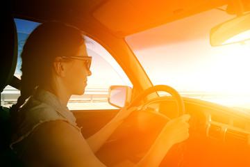 young woman driving to sunset