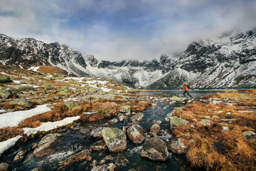 A man jumping across rocks over a lake in the High Tatras