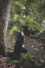 beautiful dark vampire woman with black mantle and hood