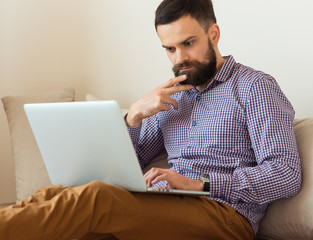 Young bearded man working on laptop at home