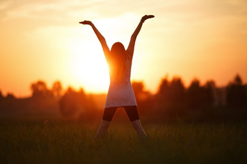 Girl with hands up on sunset background