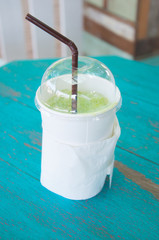 take-home cup of ice green tea on wooden table