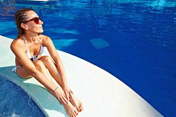 Beautiful girl relaxing near pool