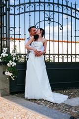 Sposi abbracciati vicino a un cancello di ferro