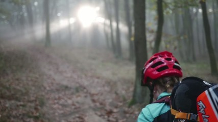 Young girl pushing her mountain bicycle slow motion during