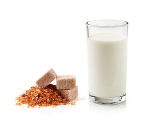 glass of milk and cane sugar isolated on white background