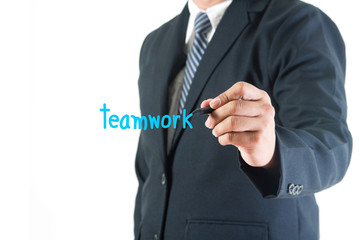 Businessman hand drawing teamwork text in a whiteboard