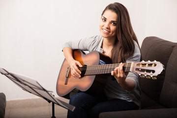 Cute girl playing guitar at home