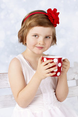 Adorable little girl drinking cocoa from red cup