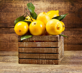 lemons with leaf in wooden box