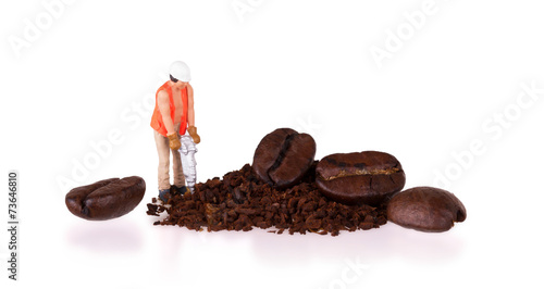 Miniature worker working on a coffee bean - 73646810