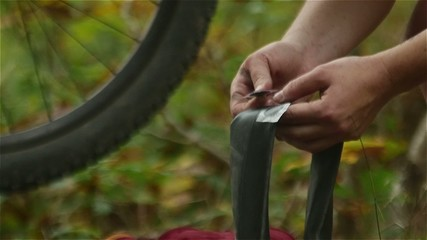 Cyclist repairing her mountain bicycle tire in slow motion close