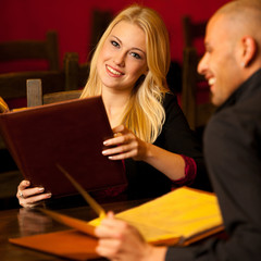 Young couple ordeting food in restaurant reading menu