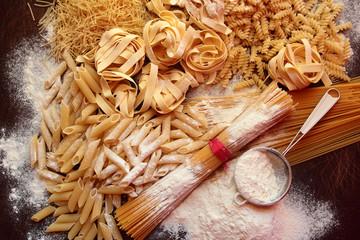 Variety of dry italian pasta on wooden board