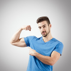 Portrait of bearded man showing arm muscle biceps