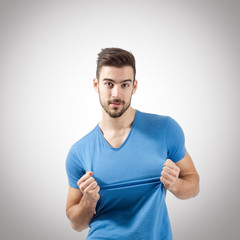 Portrait of man pulling t-shirt