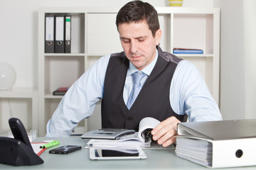 Handsome Businessman Calculating at his Worktable