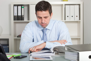 Handsome businessman reviewing report papers