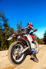 Fast moving motocross rider on dirt road.
