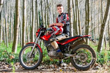 Handsome teen boy sitting on motocross motorbike.