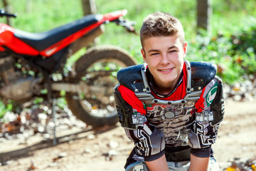 Portrait of cute motocross rider outdoors.