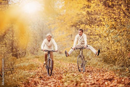 Active seniors ridding bike and having fun - 73653039