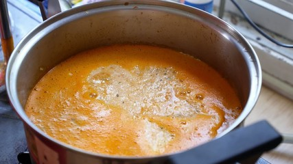 Stirring with Blender Tomato Carrot Cream Soup in Pan.
