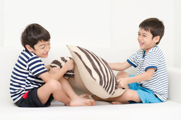 Little sibling boy playing pillow fighting on sofa