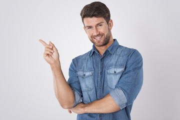 Handsome man pointing at copy space