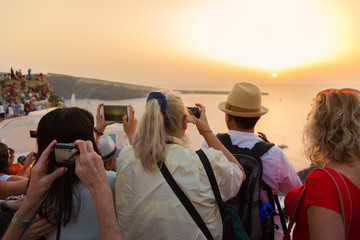 Trvellers watching sunset in Oia, Santorini, Greece.