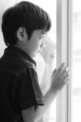 Little boy standing behind the door black and white