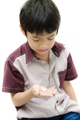 Little boy does'n want to take medicine pill on white background