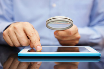 Businessman using tablet computer  with magnifying glass . Cauti